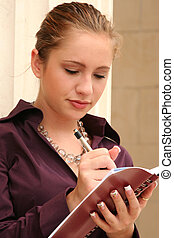 Planner - Young businesswoman writing in a day planner