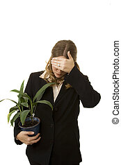 Fired - Businesswoman isolated on white holding plant...