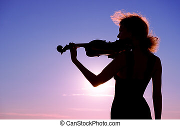 solo at sunset - violin player performing solo at sunset
