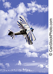 Stunt Flyer - An aerobatic airplane against a cloudy sky