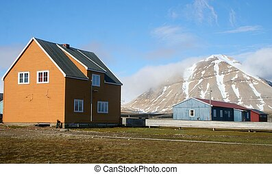 Buildings by the Mountain - Colourful buildings near a...