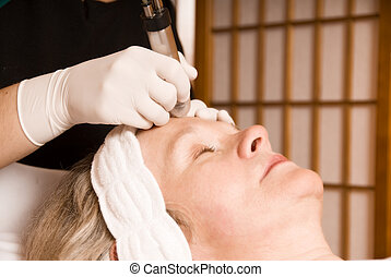 beauty treatment - older woman getting electrolysis on he...