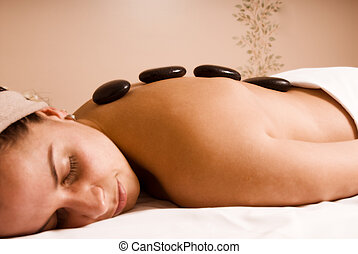 Hot stone - young woman getting a stone massage at a spa