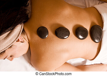 Hot stones - young woman getting a stone massage at a spa