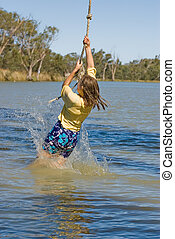 girl swinging - a teenage girl is swinging on a rope over a...