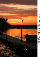 Sunset on the dock - Setting sun casting orange hues on a...