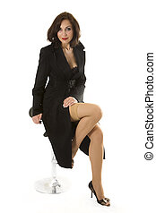 Fashion model in a black coat poses in studio