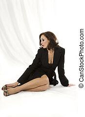 Fashion model in a black coat poses in studio