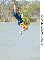 girl swinging over river - a teenage girl is swinging on a...