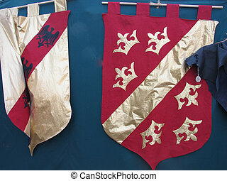 Medieval flags in red and gold hanged on a tent