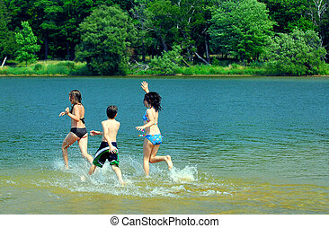 Children in a lake - Group of young children running into...