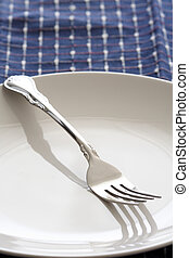 Fork and plate - A shot of a fork on an empty plate on top...