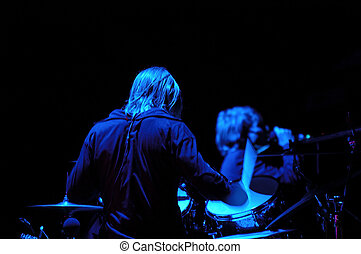 Drummer and blue light - Drummer is playing in a band. The...
