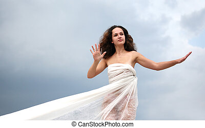 Desire to fly - The girl in a white fabric on a background...