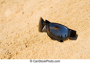 Sunglasses reflecting beach view