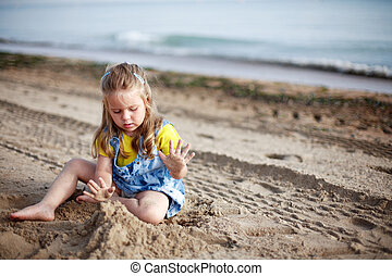 Kid playing on beach - Cute kid playing with sand on a beach