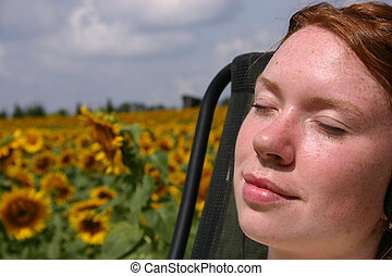 Warmth of the Sun - a young lady relaxing by a field of...