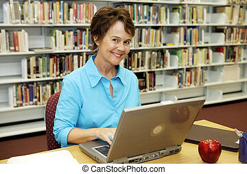 School Library - Teacher - A pretty librarian working on her...