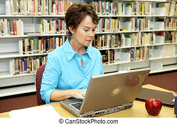 School Library - Research - A pretty school librarian doing...