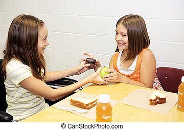 School Lunch - Trade - Two school girls at lunch trading...