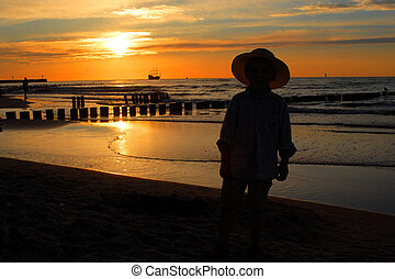 Sunset at the seaside - Child with a hat at the seaside,...