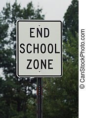 End School Zone sign against trees and sky