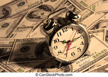 Clock Over Money - An alarm clock over a hundred dollar bill...