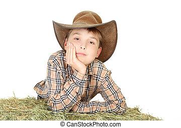 Farm boy leaning on lucerne bale