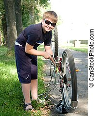 boy repairs a bicycle - little boy repairs a bicycle in a...