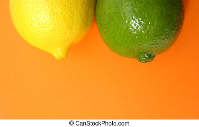 Citrus Fruit Duo - fresh lemon and lime fruit on contrasting...