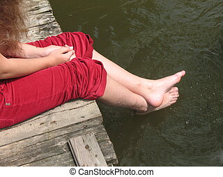 Girl\\\'s feet - A young girl sits on the bridge by the...