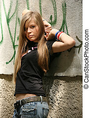 The girl - teenager on a background of a wall