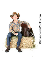 Boy on hay bale with saddle - Country boy sitting on a hay...