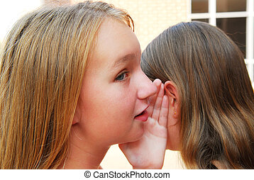 Gossiping - Two young teenage girls gossiping in school yard