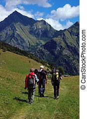 Trekkers walking along a mountain path, west Alps, Italy.