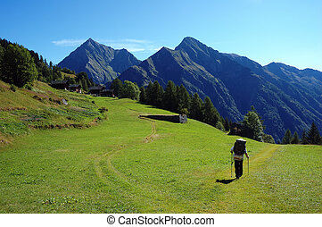 Trekker walking along a mountain path, west Alps, Italy.