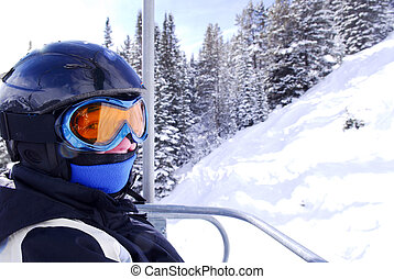 Happy skier - Young girl in downhill ski gear on a chairlift...