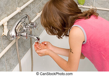 Dental hygiene - Young child brushing her teeth in bathroom