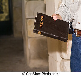 Holding the Word - A man within room of stone walls holding...
