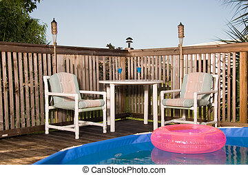 Poolside - Patio furniture at pool side on deck