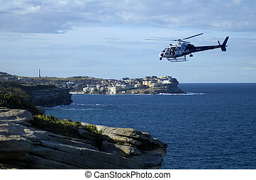 coast guard - police helicopter flying above rocky...