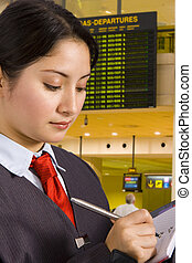 Businesswoman in airport - businesswoman writing a report in...