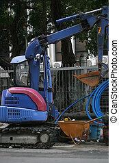 blue power shovel along side of a road