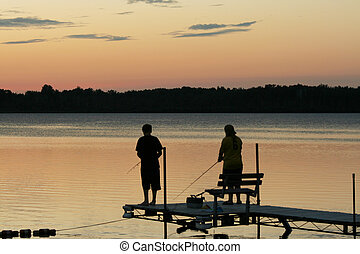 Children fishing - Two children fishing at sunset off the...