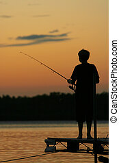 Fishing at Sunset - Young boy fishing off the pier at...