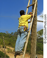 Asian electricity worker - Asian workman on a ladder working...
