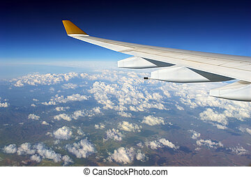 Airplane wing over clouded globe - Commercial airplane wing...