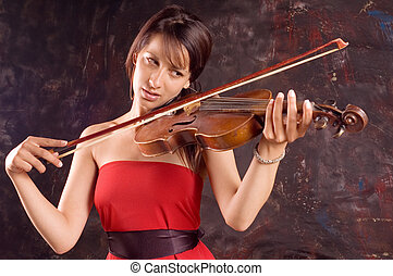 Girl with violin - A young brunette woman playing solo her...