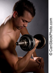 Biceps exercises - Handsome young man doing biceps exercises...