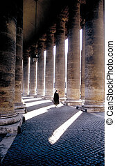 St Peters, Rome - Nun walking alone through colonnade at St...